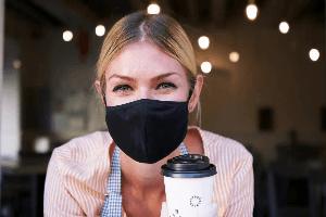 אישה עם מסיכת קורונה וקפה